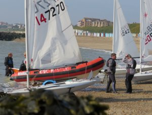 Rob Lockett launches his Laser whilst the race winner - Ken Potts has a few words to say to a fellow competitor