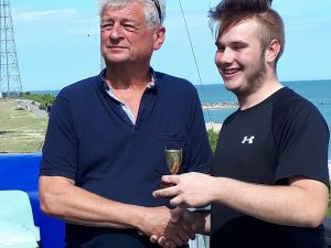 Gunfleet Cadet Michael Gutteridge is presented with the Clacton Sailing Club Regatta CUDC Cadet Cup by CSC Commodore Martin Chivers